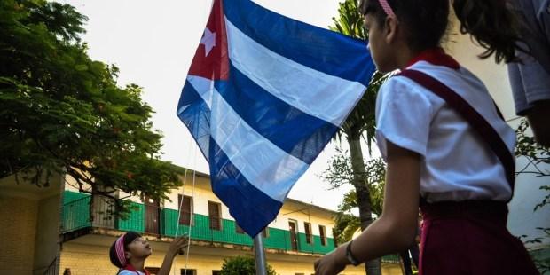 Niñas alzando la bandera cubana