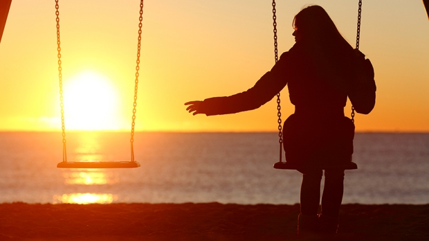 Single or divorced woman alone missing a boyfriend while swinging on the beach at sunset © Antonio Guillem / Shutterstock