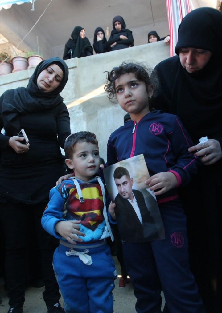 Ali et Malak, les enfants d'Adel Termos, tué dans le double attentat-suicide du quartier de Burj al-Barajneh à Beyrouth le 12 novembre 2015, portant un portrait de leur père durant ses funérailles © AFP PHOTO / MAHMOUD ZAYYAT