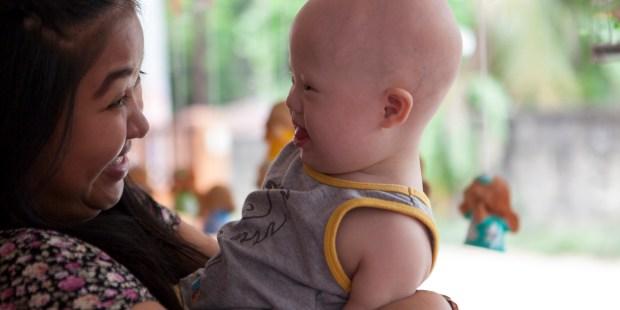 Gammy, le bébé trisomique abandonné à sa naissance par le couple australien Farnell à sa mère porteuse (Pattaramon Chanbua), avec cette dernière dans la nouvelle maison familiale à Chonburi (Thaïlande) le 23 avril 2015