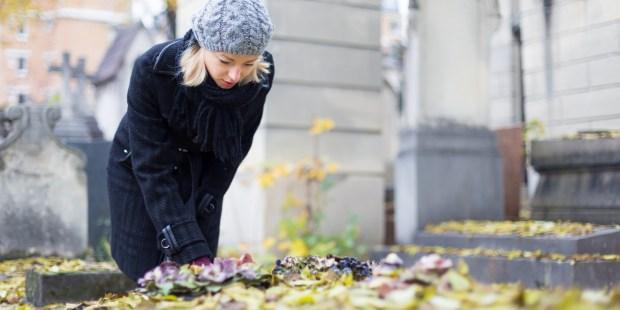 Femme pleurant devant une tombe