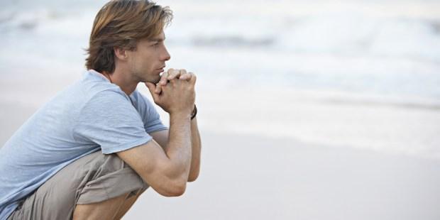 Homme méditant sur la plage