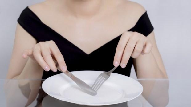 Femme devant une assiette vide