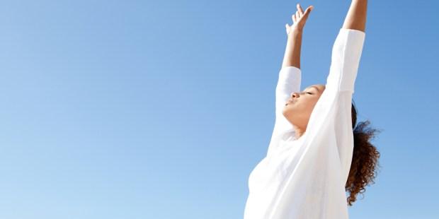 Jeune femme respirant les bras en l'air
