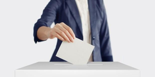 Femme glissant son bulletin de vote dans l'urne