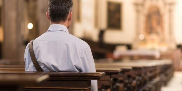Homme seul, de dos, dans une église.