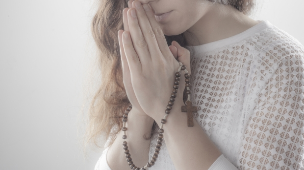 Femme priant avec un chapelet
