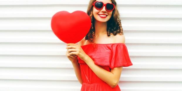 Femme habillée en rouge et tenant un coeur