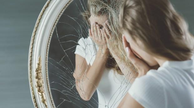 Jeune fille complexée devant un miroir brisé