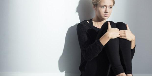 Jeune femme seule adossée à un mur