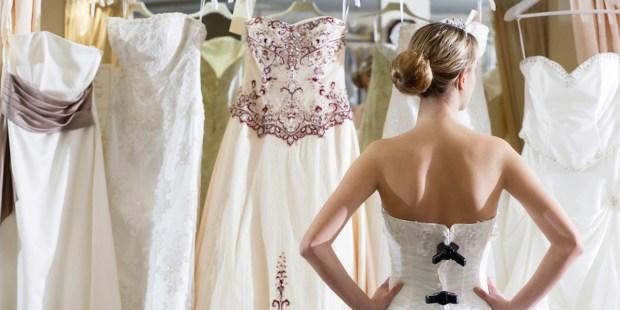 Dziewczyna przymierza suknię ślubne w showroomie i patrzy na wieszak z innymi sukniami.