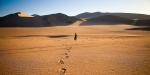 WALKING ALONE IN THE DESERT WITH FOOTSTEPS