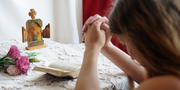 Young girl praying at home