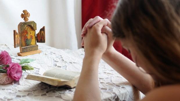 Young girl praying at home