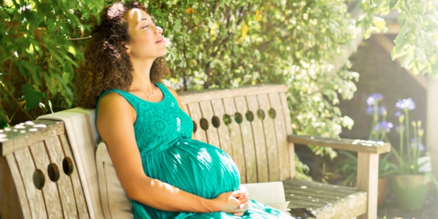 PREGNANT WOMAN SITTING IN PARK