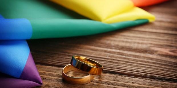 WEDDING RINGS AND RAINBOW GAY FLAG