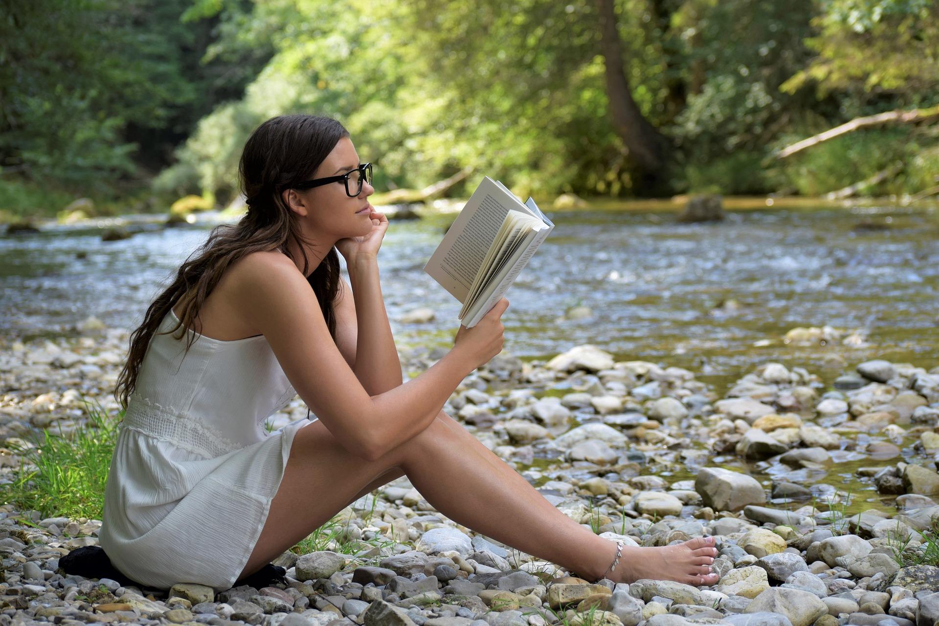 GIRL READING RIVER