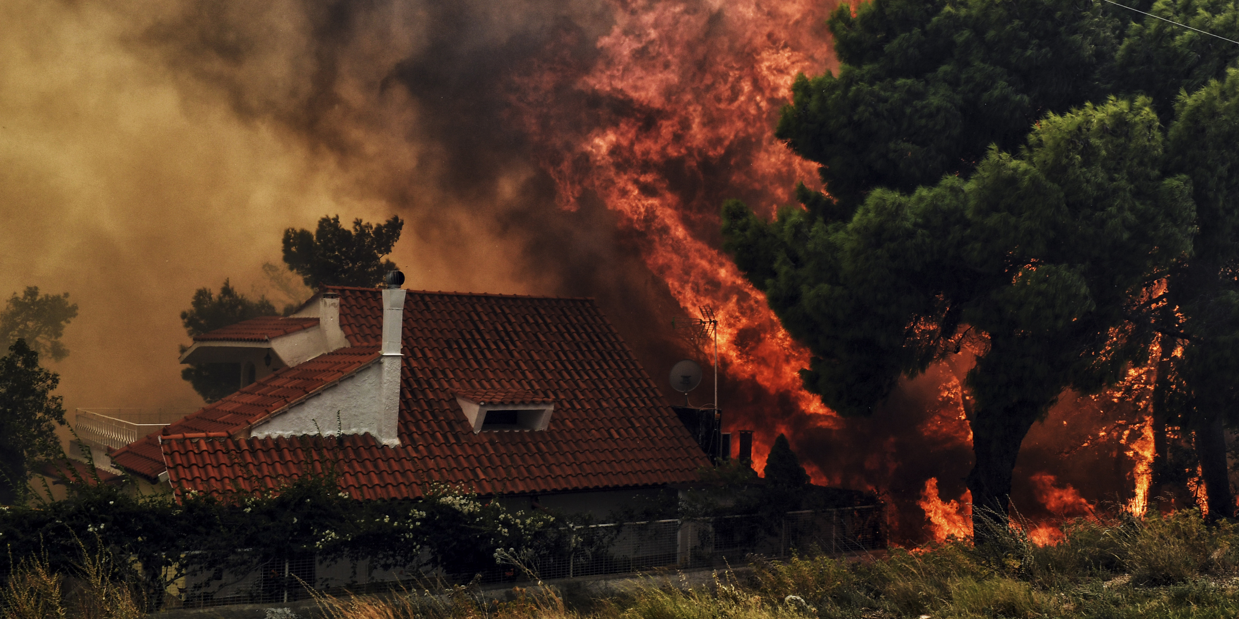 """A house is threatened by a huge blaze during a wildfire in Kineta, near Athens, on July 23, 2018. More than 300 firefighters, five aircraft and two helicopters have been mobilised to tackle the """"extremely difficult"""" situation due to strong gusts of wind, Athens fire chief Achille Tzouvaras said. / AFP PHOTO / VALERIE GACHE"""