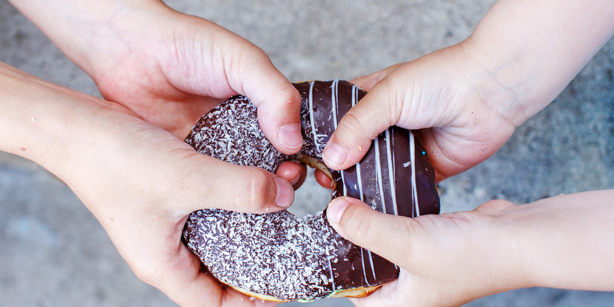 children's hands holding a chocolate donut. two kids pull to themselves donut. closeup.the concept of sharing food
