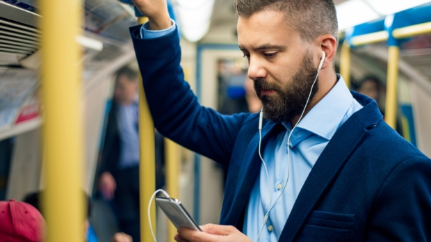 Jeune homme lisant dans le métro