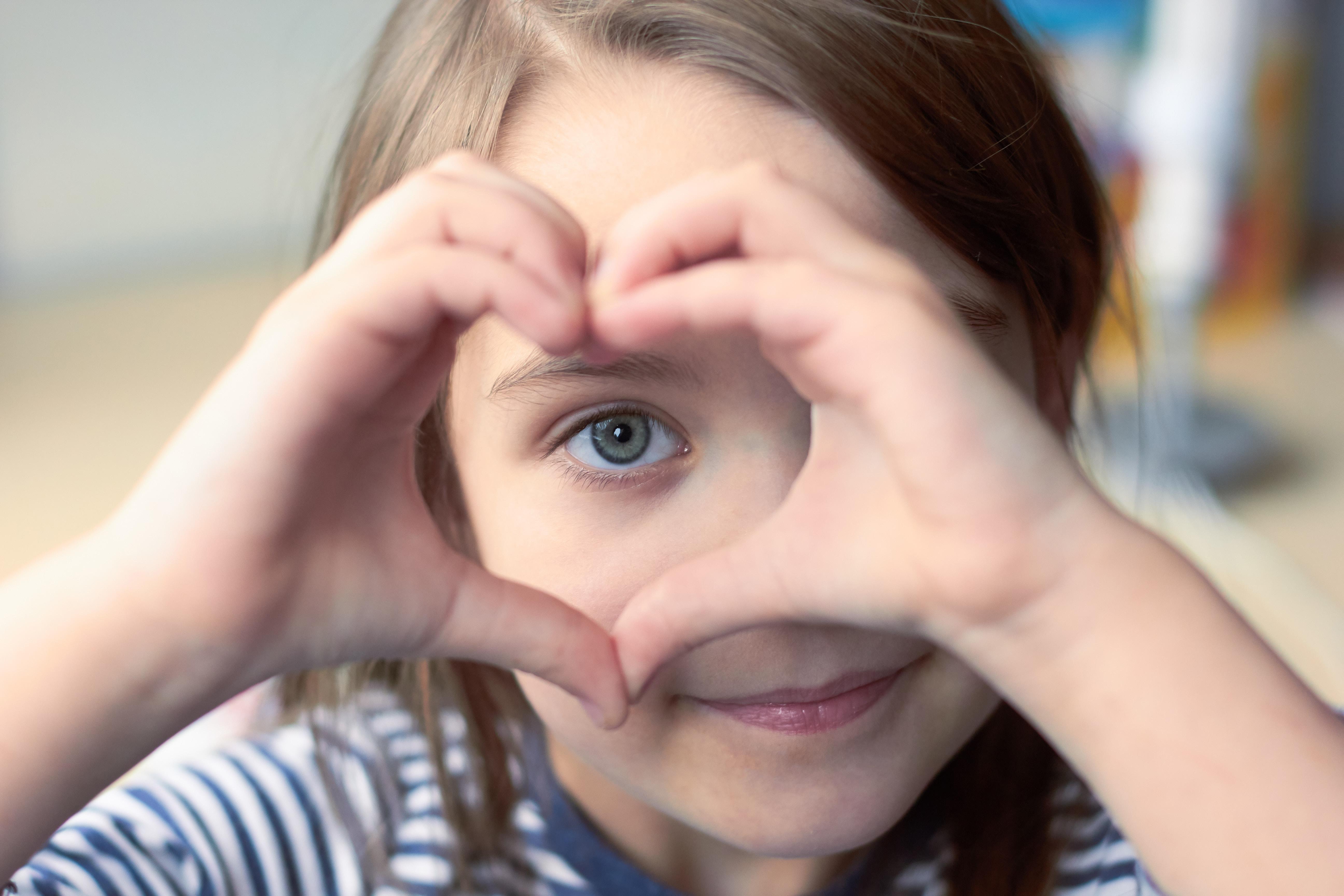 enfant faisant un coeur avec ses mains