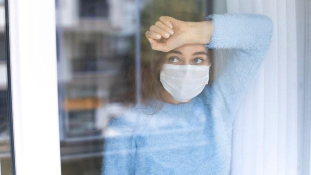 femme à la fenêtre avec un masque