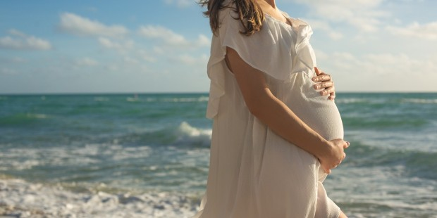 Happy Young Pregnant Woman on the Beach at the Atlantic Ocean